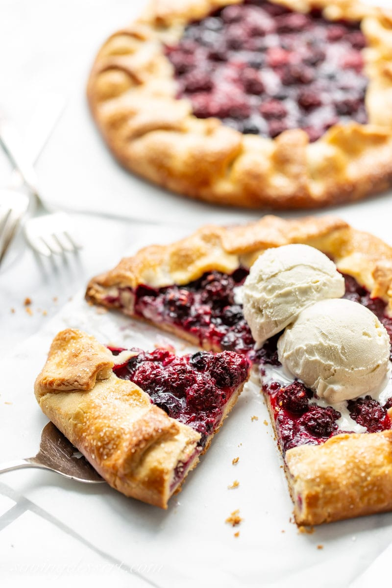 A sliced mixed berry crostata topped with vanilla bean ice cream