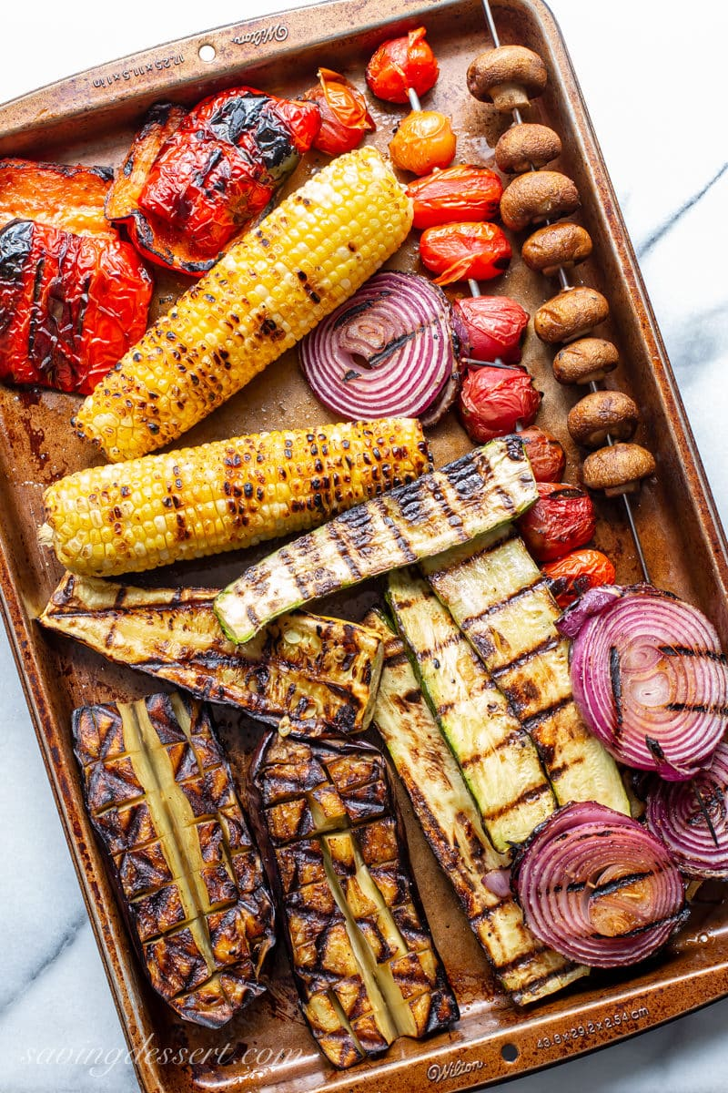 A tray of grilled corn, onion, tomatoes, mushrooms, peppers, squash and eggplant