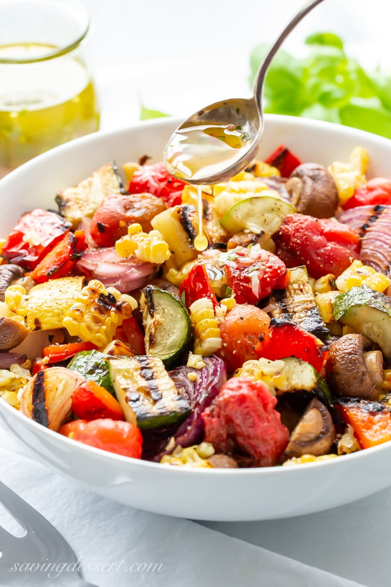 A bowl of chopped grilled vegetable including zucchini, corn, mushrooms and peppers
