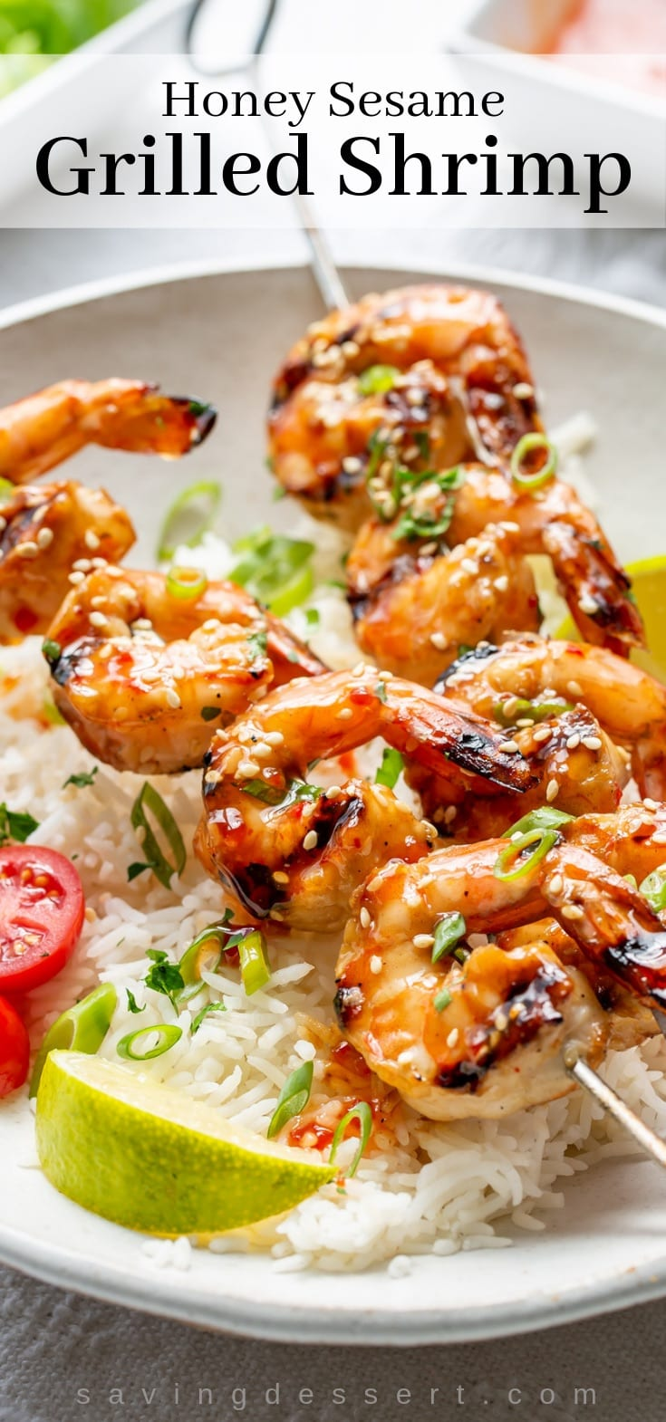 Honey Sesame Grilled Shrimp on skewers over a bowl of rice with lime wedges and sliced tomatoes