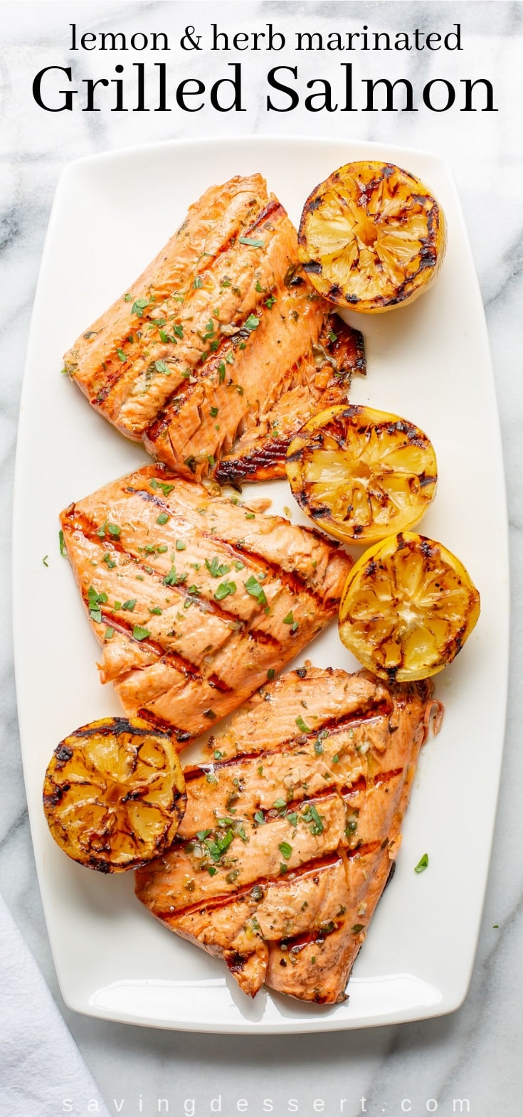 A platter with grilled salmon and lemons garnished with fresh parsley