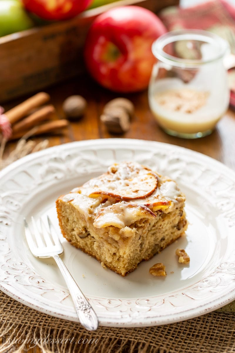 A piece of apple sheet cake with walnuts and sliced apples on top