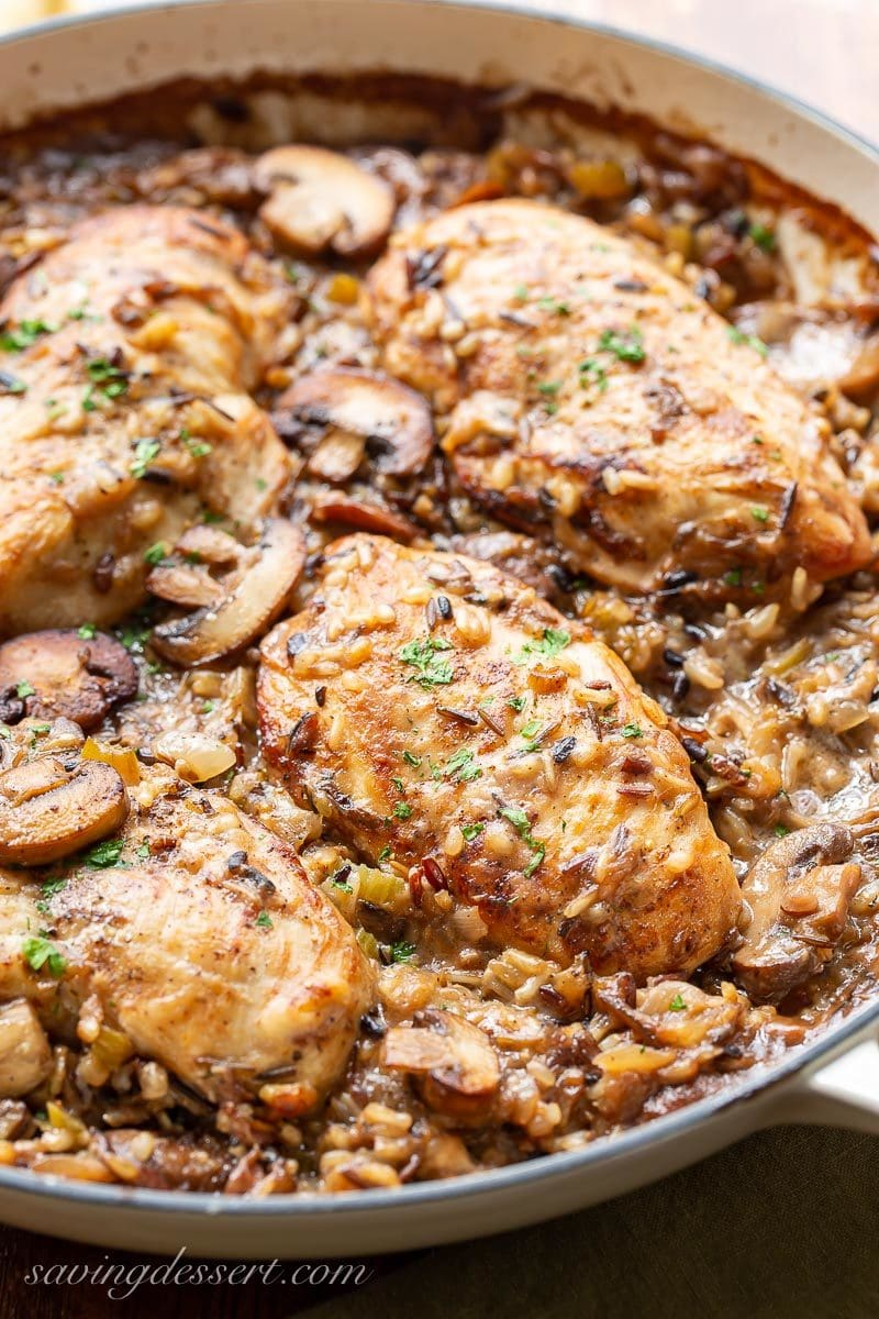 A skillet with chicken breasts, mushrooms and wild rice casserole