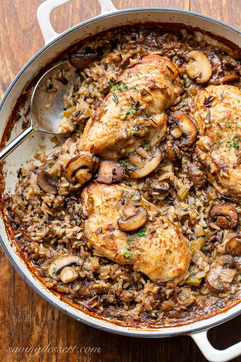 A skillet filled with mushrooms and wild rice topped with chicken breasts