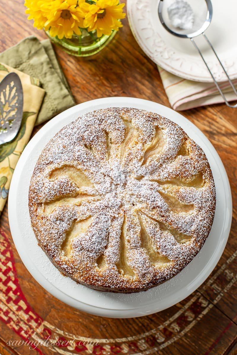 An overhead view of a fresh pear cake dusted with powdered sugar