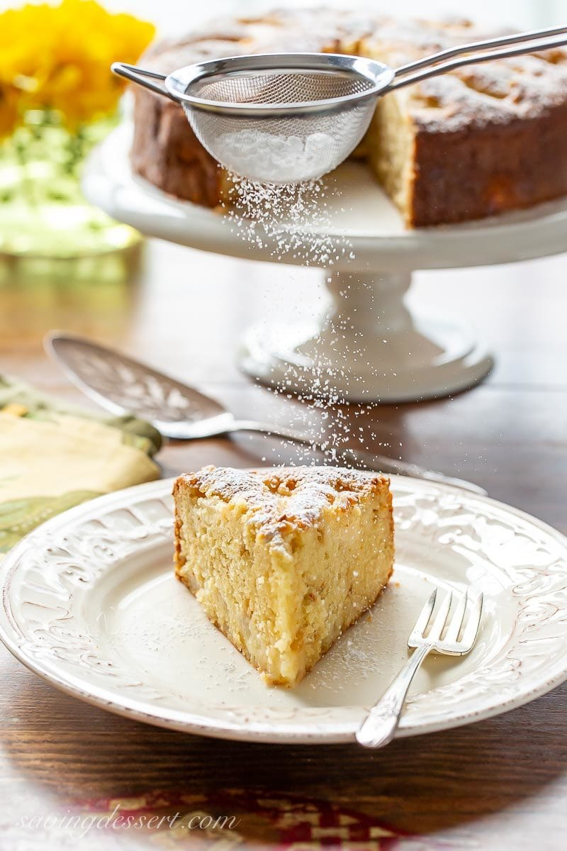 A slice of fresh pear cake being dusted with powdered sugar