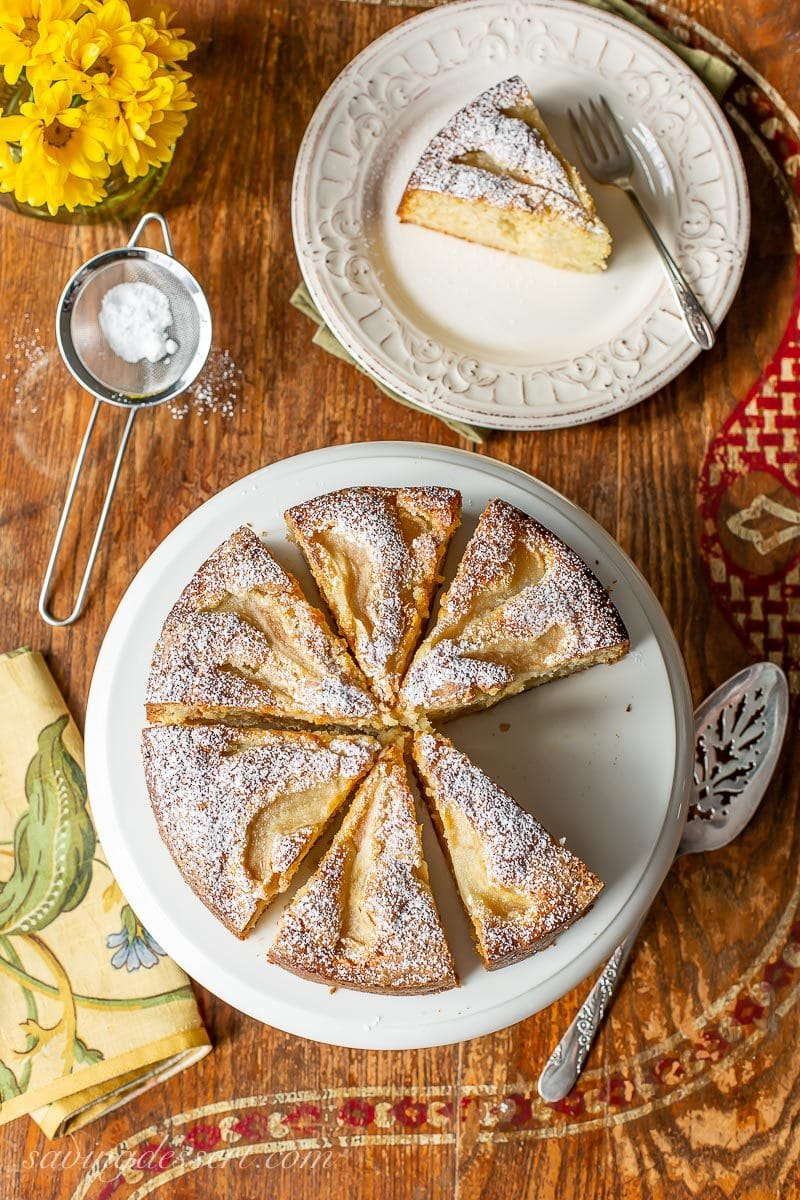 An overhead shot of a sliced fresh pear cake dusted with powdered sugar