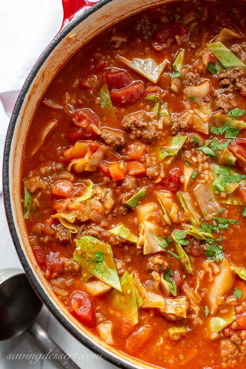 A close up of a pot of cabbage roll soup with carrots, tomatoes, rice and parsley