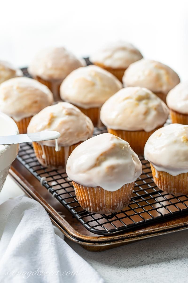 Big domed muffins with a vanilla glaze on a cooling rack