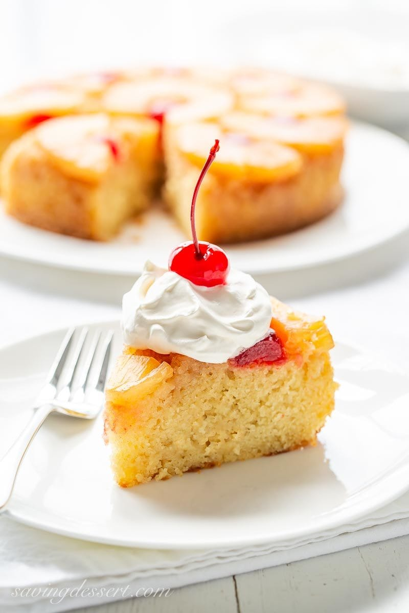A slice of pineapple upside down cake with whipped cream and a cherry on top