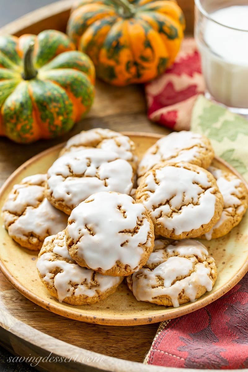 A plate of Spiced Pumpkin Oatmeal Cookies with pumpkins and a glass of milk