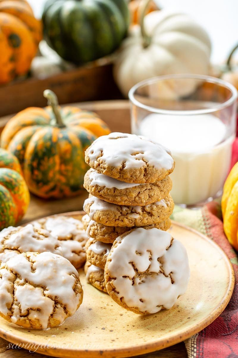 A stack of iced Spiced Pumpkin Oatmeal Cookies with a glass of milk and ornamental pumpkins