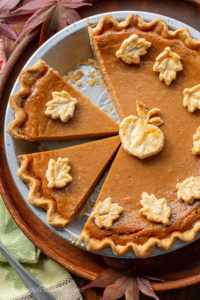Sliced apple butter pie decorated with pastry crust cut-outs in the shape of leaves and an apple