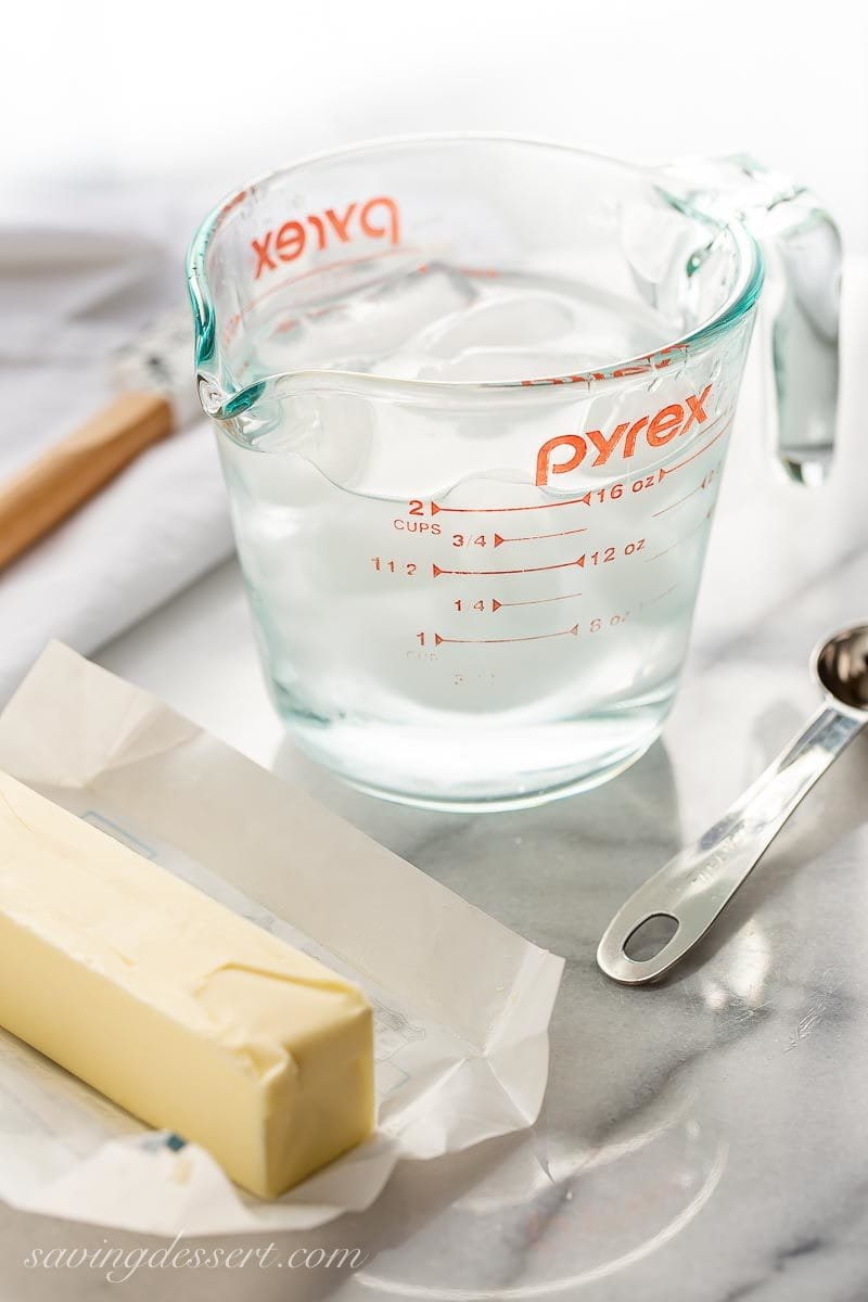 A glass measuring cup with a spout filled with ice water, and a stick of cold butter to represent one of our best baking tips