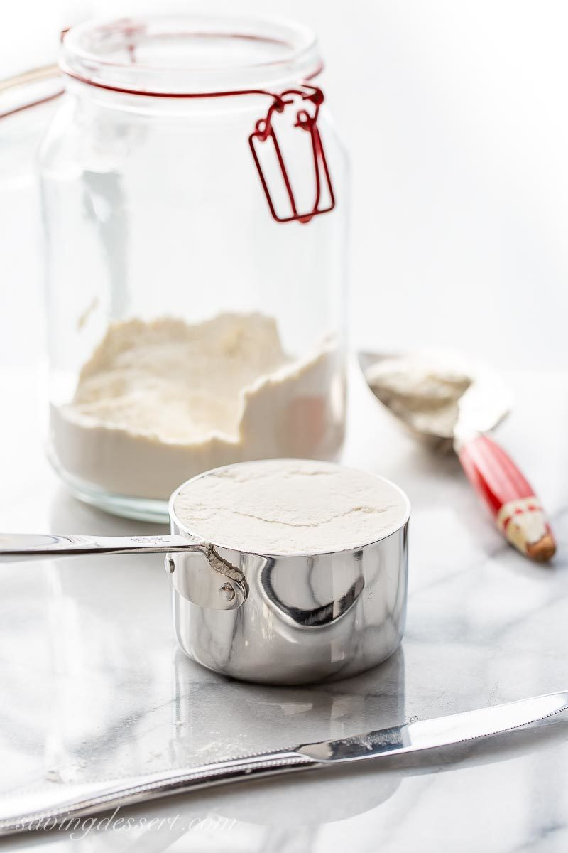 A jar of flour and a measuring cup