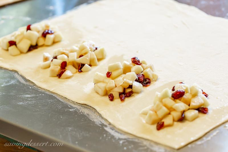 A piece of puff pastry rolled out and topped with a cranberry apple filling