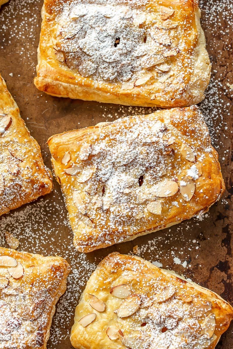 Apple cranberry puff pastry tarts dusted with powdered sugar on a baking pan