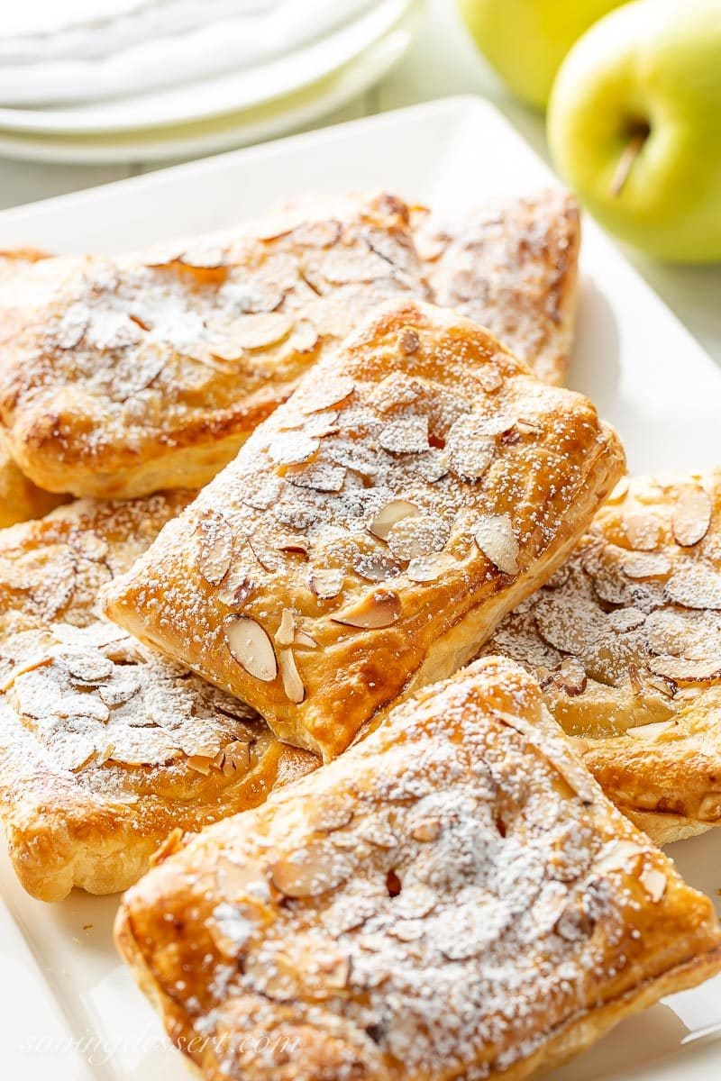 A platter of fresh made apple puff pastry tarts topped with sliced almonds and sprinkled with powdered sugar