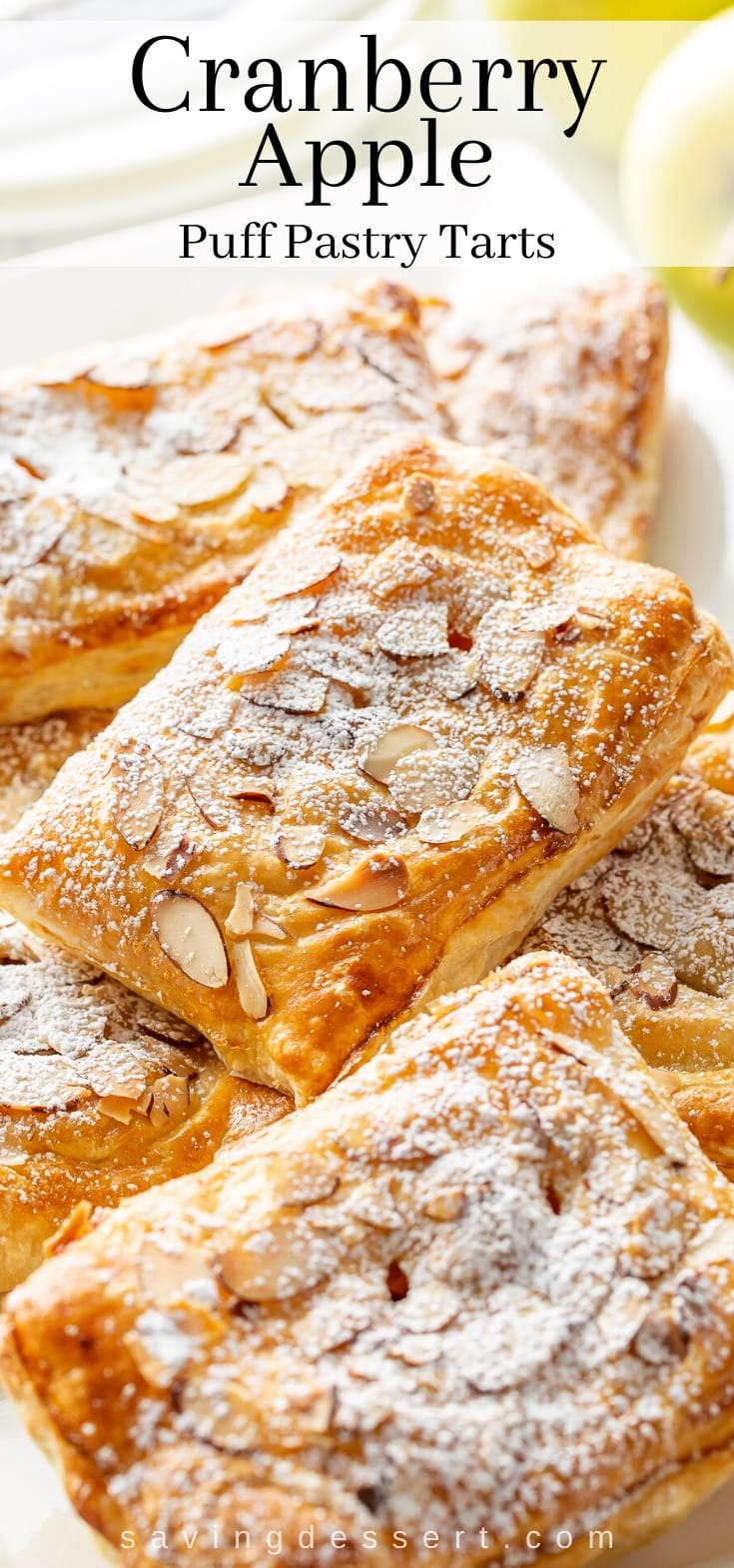 A platter of apple and cranberry puff pastry tarts dusted with powdered sugar and topped with sliced almonds