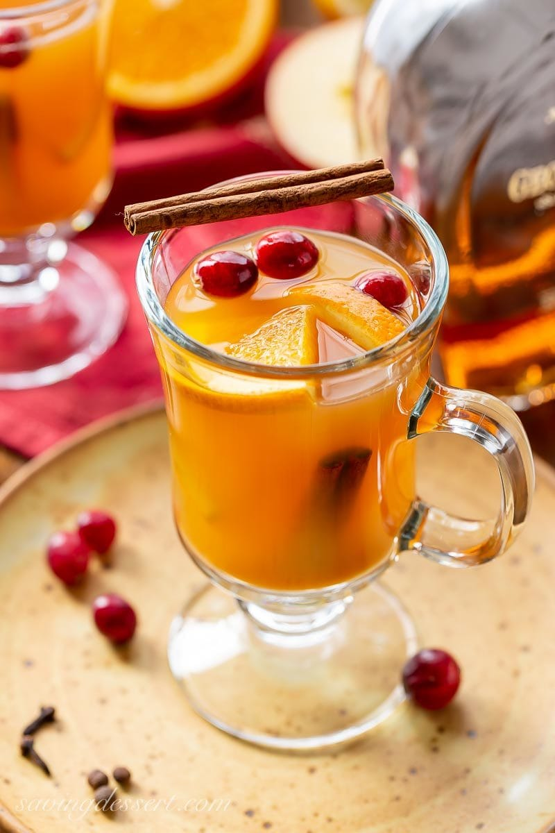 A mug of hot spiced apple cider garnished with orange slices, cinnamon sticks and a few fresh cranberries