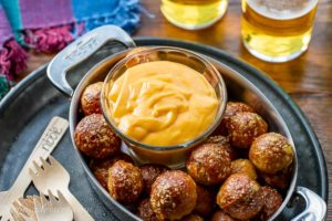 A small bowl of beer cheese dip served with pretzel nuggets