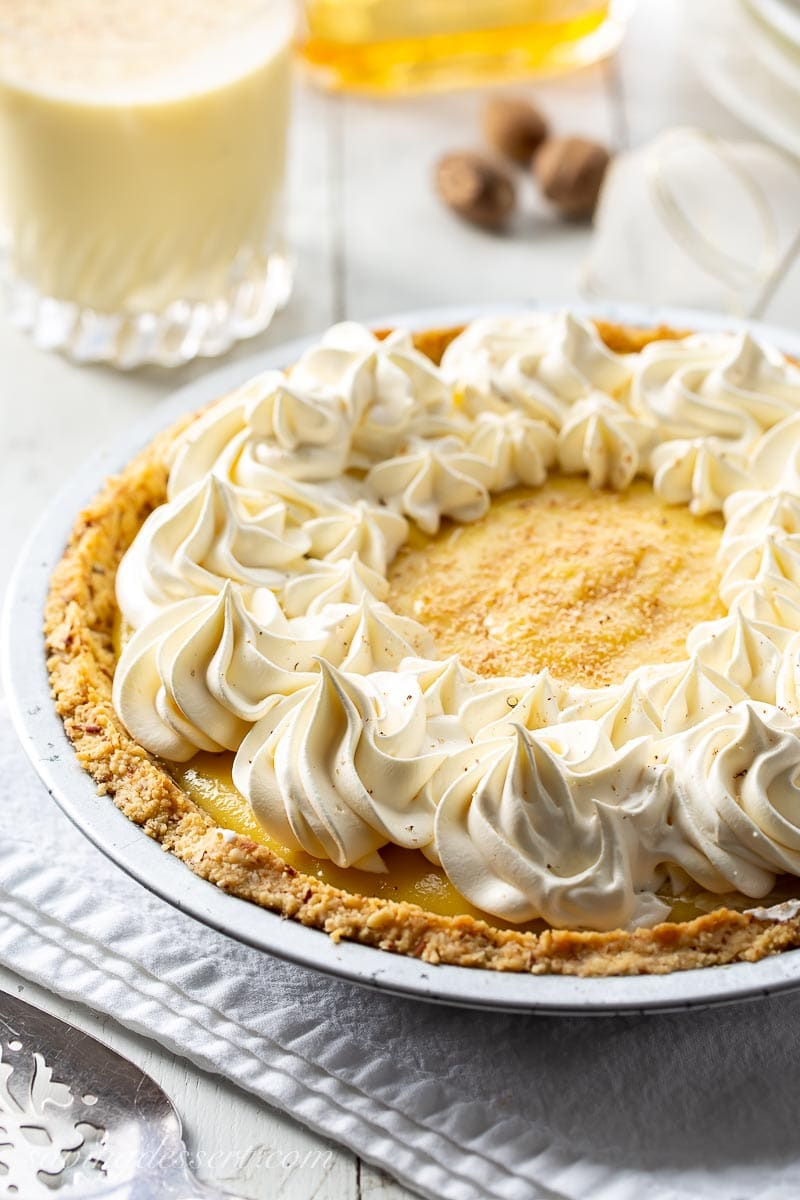 A creamy eggnog pie topped with whipped cream and fresh grated nutmeg
