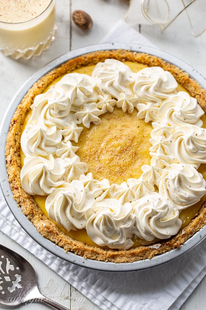 An eggnog pie with crushed cookie crust topped with swirls of whipped cream and fresh grated nutmeg