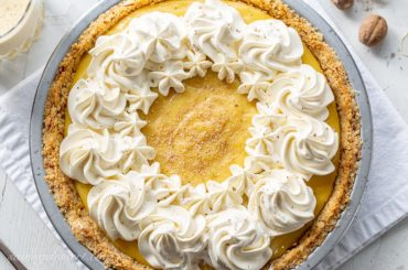 Creamy eggnog pie with swirls of whipped cream and nutmeg