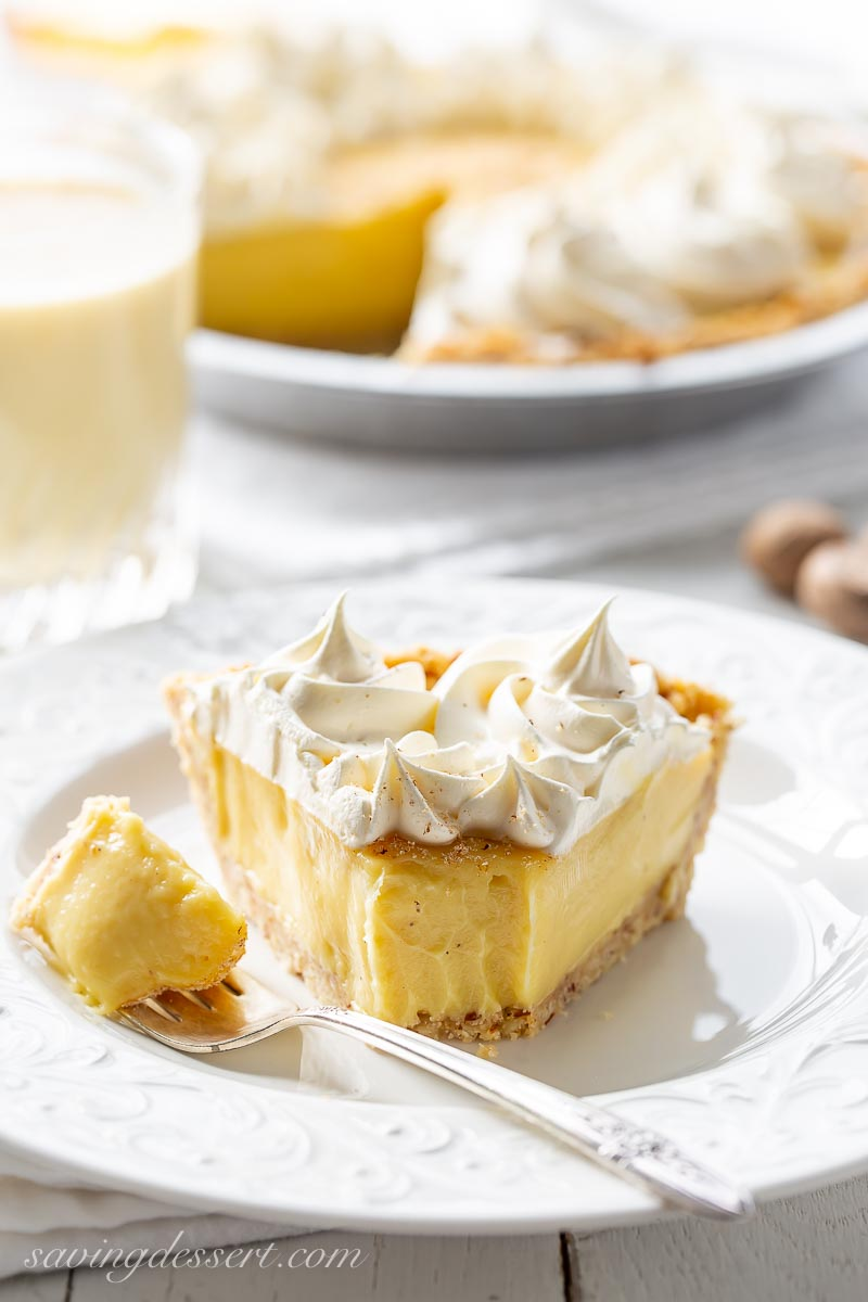 A slice of eggnog pie topped with whipped cream and fresh grated nutmeg
