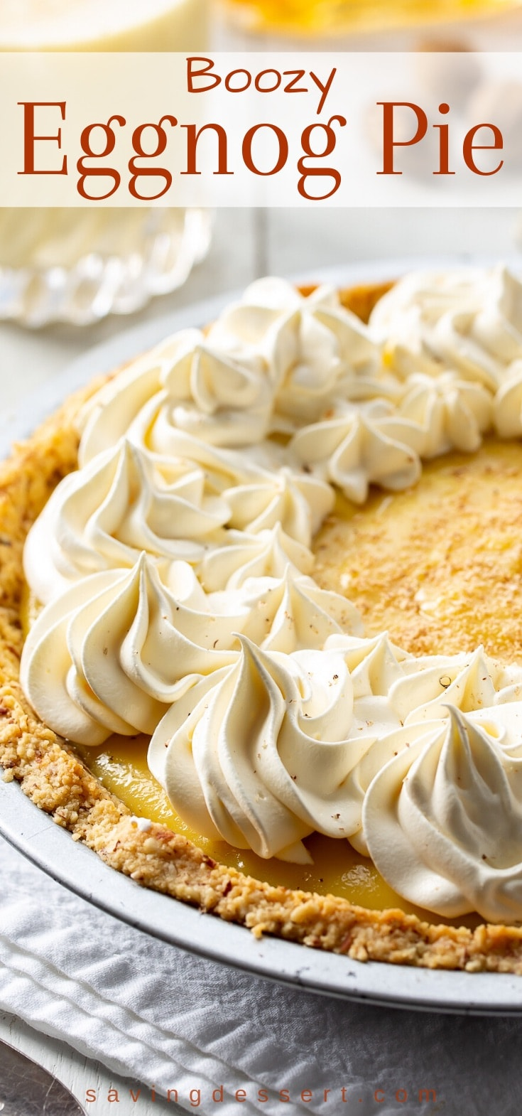 A creamy, boozy eggnog pie topped with swirls of whipped cream and fresh grated nutmeg