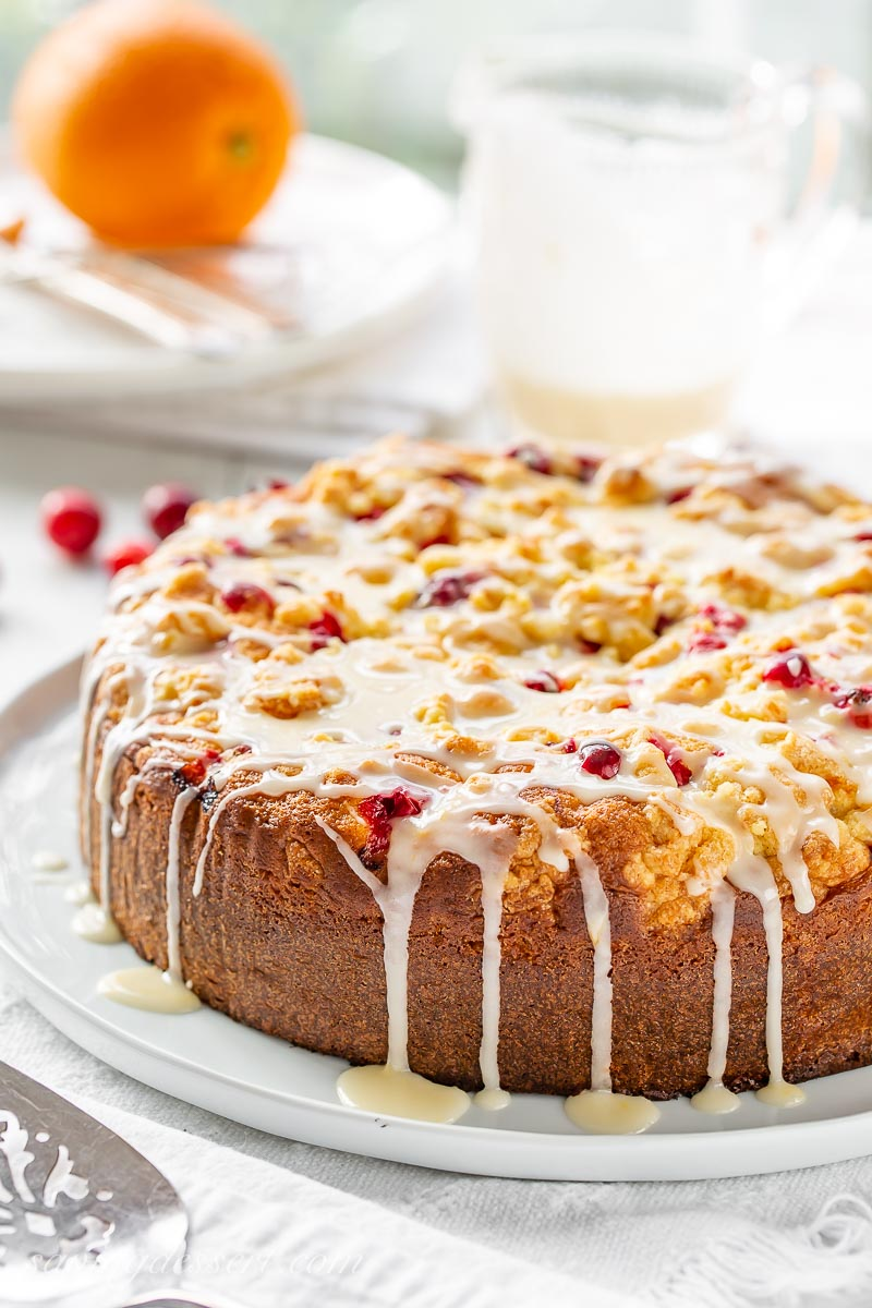A side view of a tall cranberry cake drizzled with orange icing