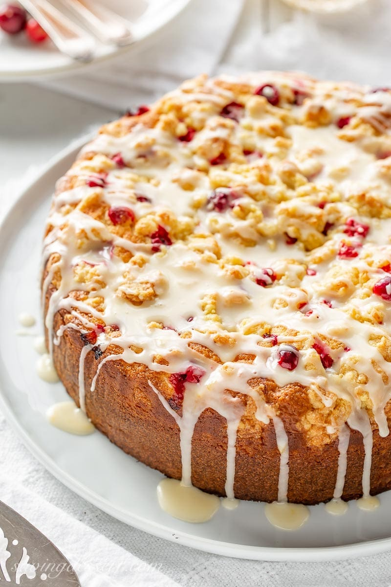 A cranberry cake with orange zest and a crumble top drizzled with an orange glaze