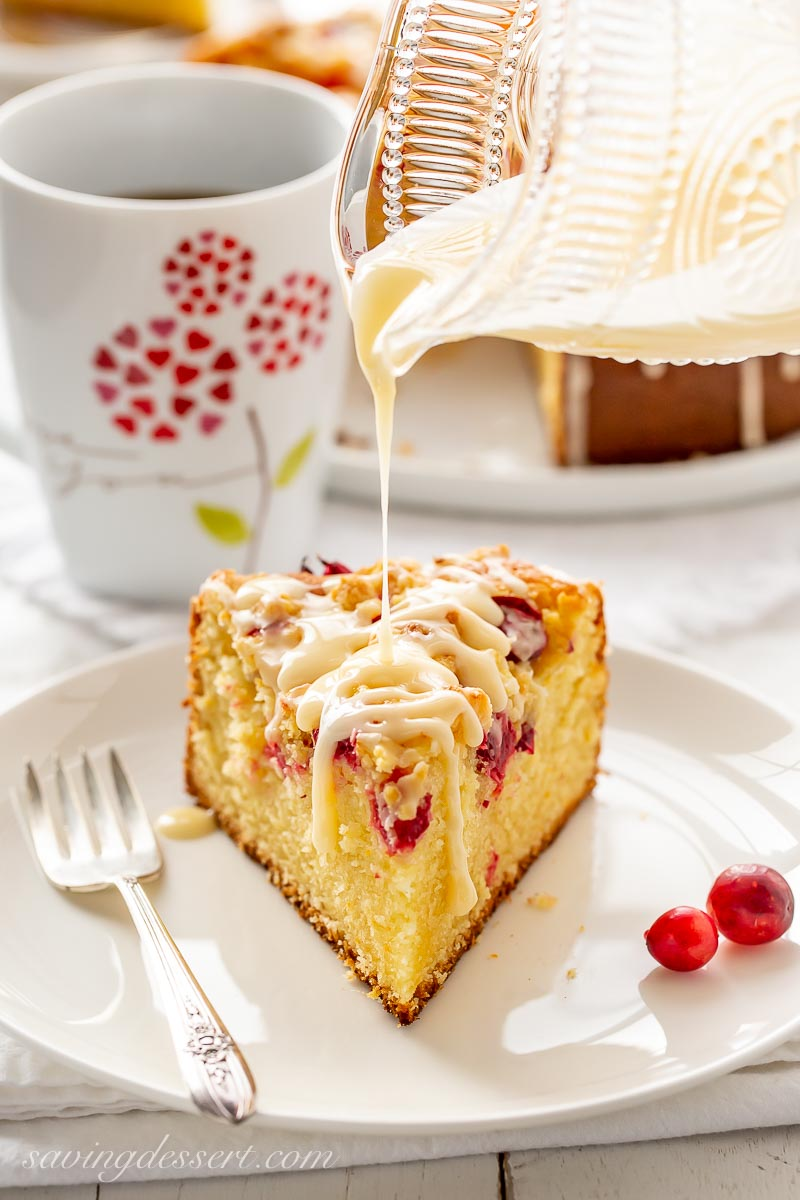 A slice of cranberry cake being drizzled with icing