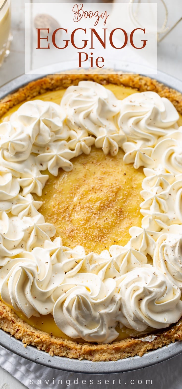 An overhead view of a creamy eggnog pie decorated with whipped cream swirls and a dusting of nutmeg