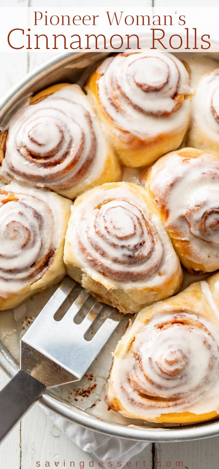 An overhead view of a pan of iced cinnamon rolls with a spatula