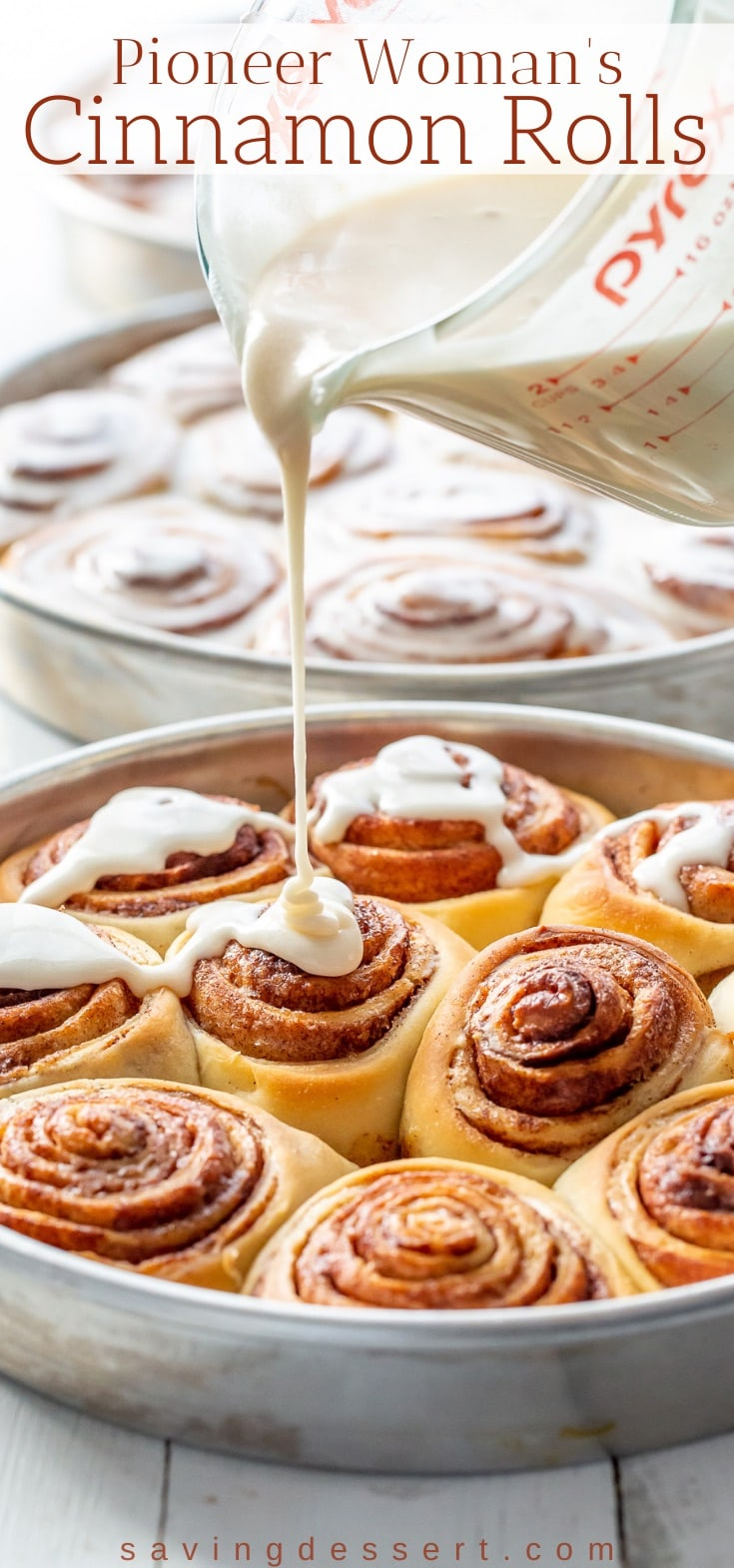 A pan of fresh baked cinnamon rolls being drizzled with icing