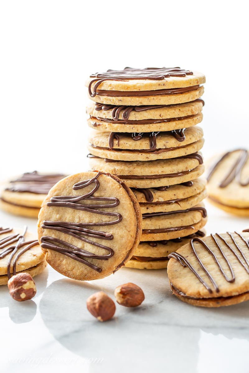 A stack of Hazelnut Nutella sandwich cookies with a decorative drizzle of chocolate on top