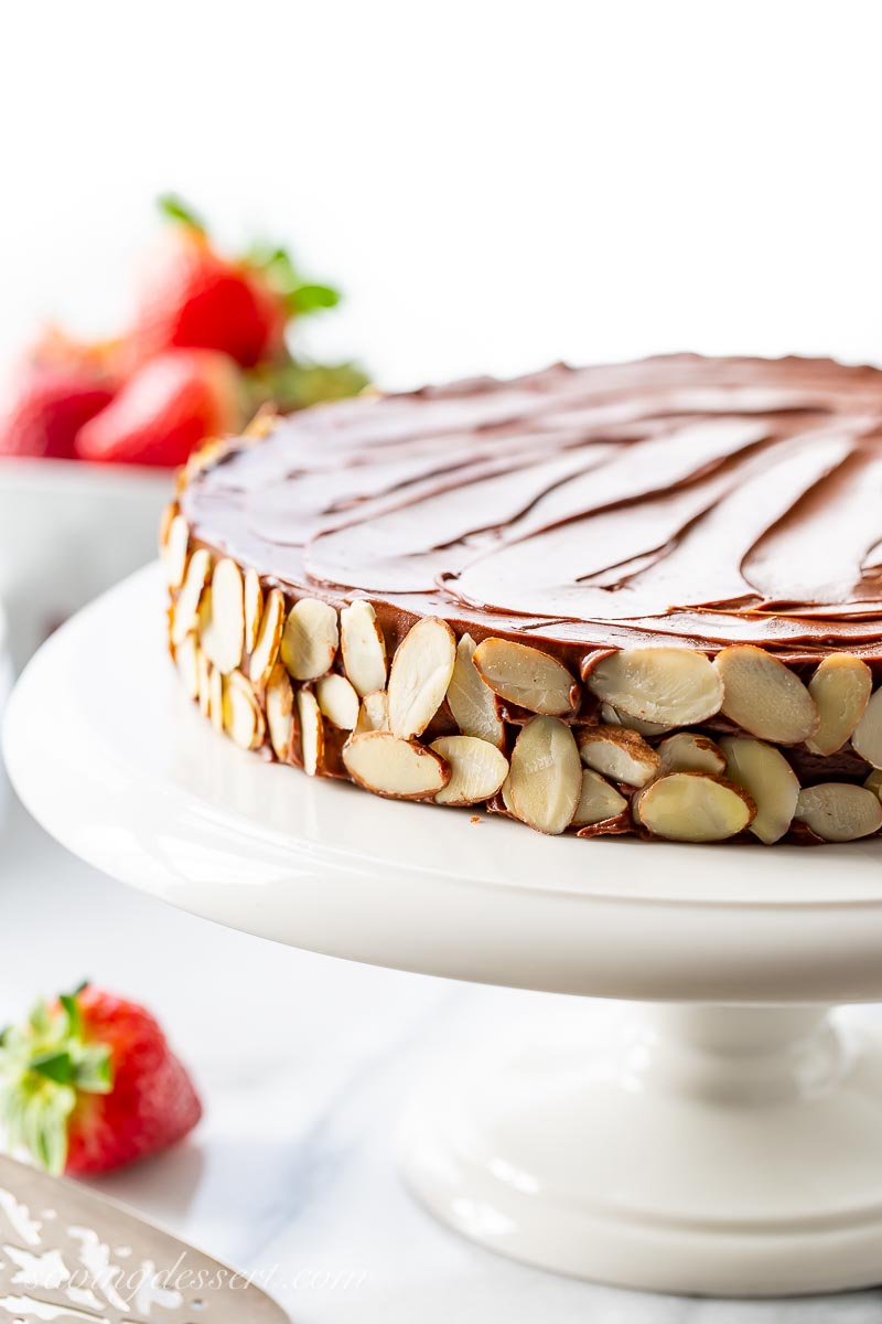 A single layer chocolate cake decorated with sliced almonds
