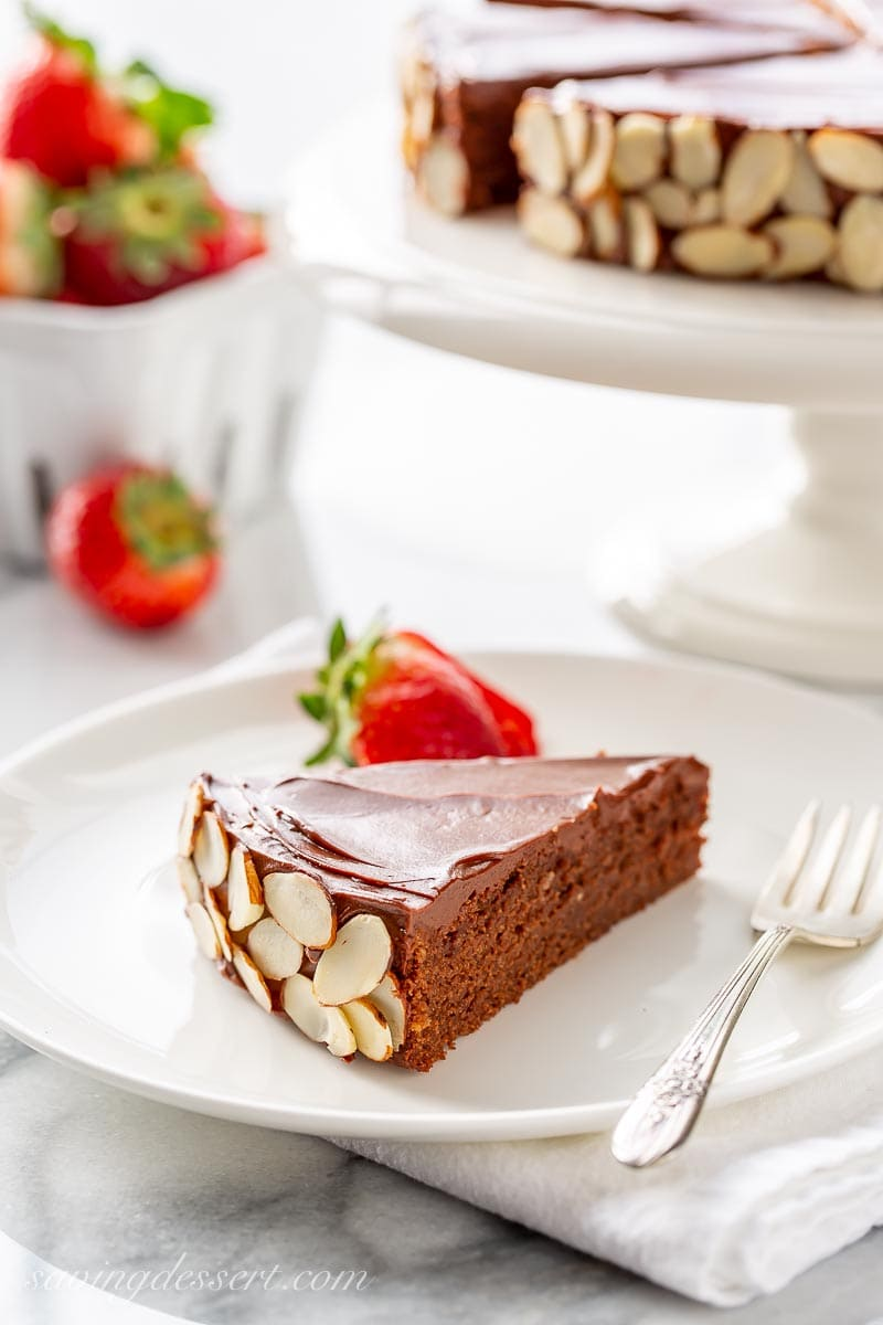 A slice of chocolate almond cake served with strawberries
