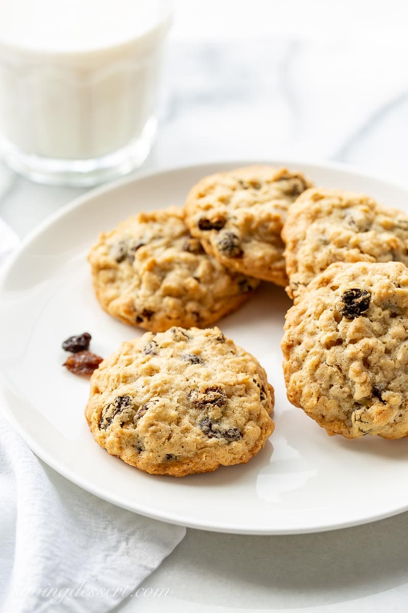 Oatmeal raisin cookies on a plate with a glass of milk