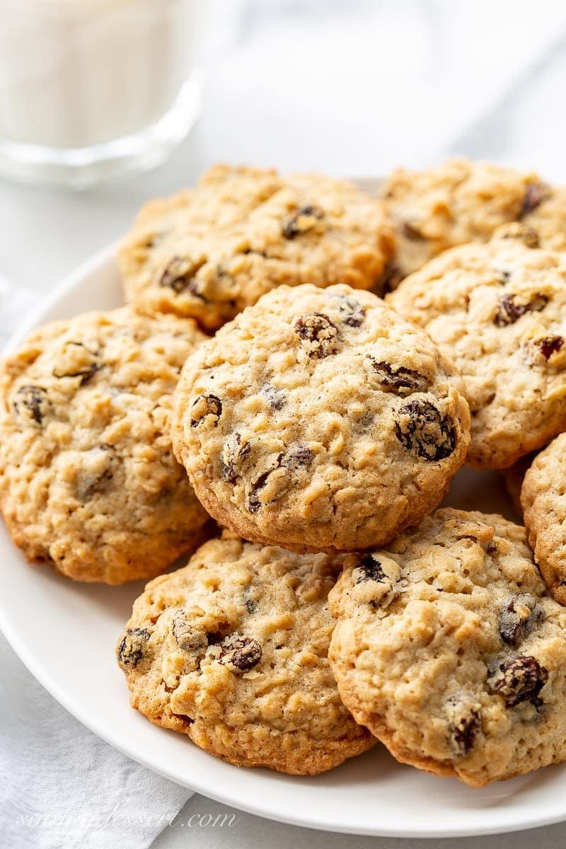A plate of oatmeal raisin cookies with a glass of milk