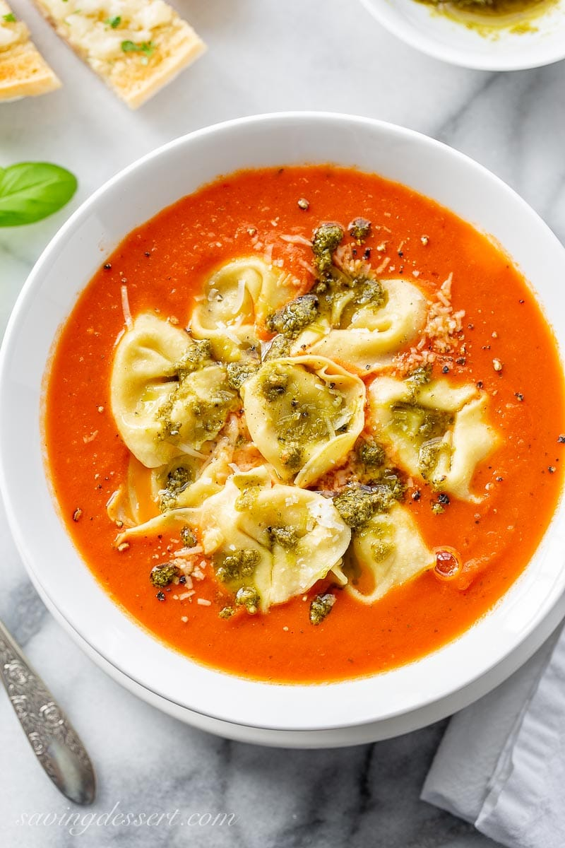 A bowl of homemade tomato soup topped with tortellini, pesto and Parmesan