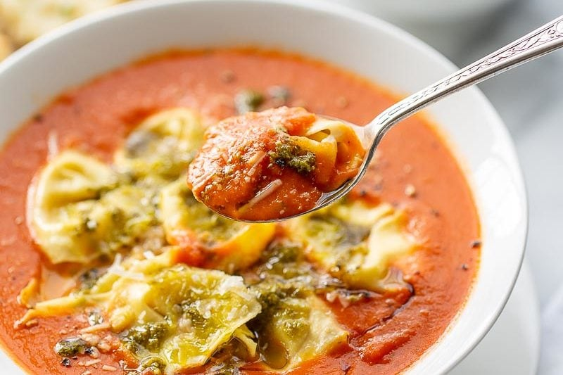 A spoonful of tortellini tomato soup topped with pesto and Parmesan
