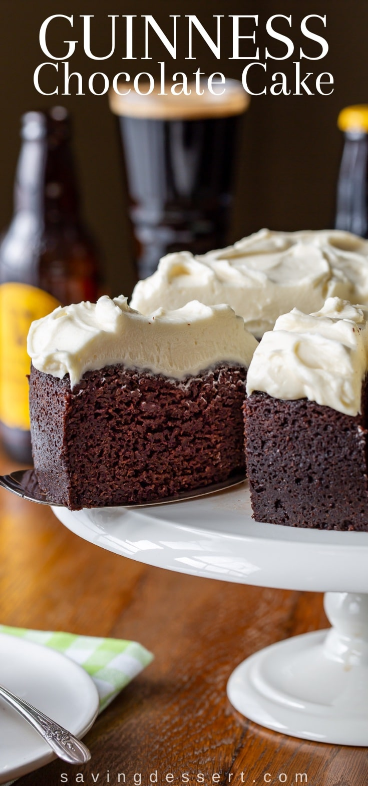 A sliced chocolate cake with white frosting on a cake stand