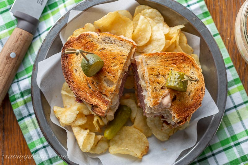 A toasted and sliced Reuben sandwich with chips and pickles