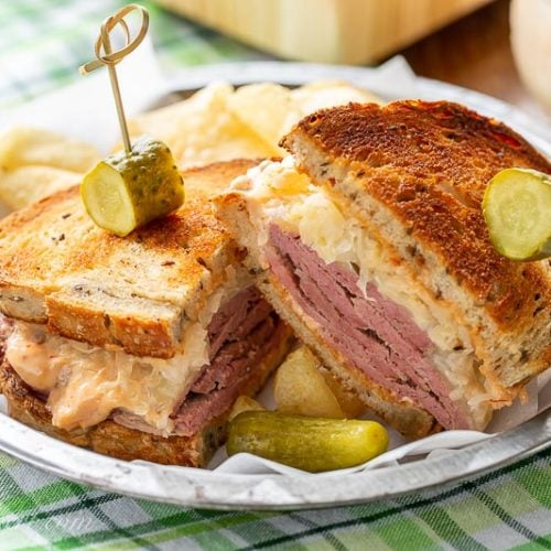 A sliced corned beef sandwich served with chips and a pickle