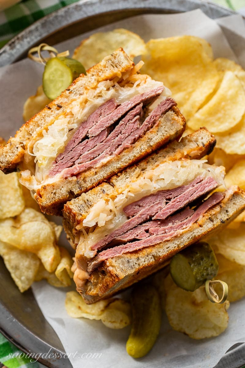 A sliced Reuben sandwich served with chips and pickles