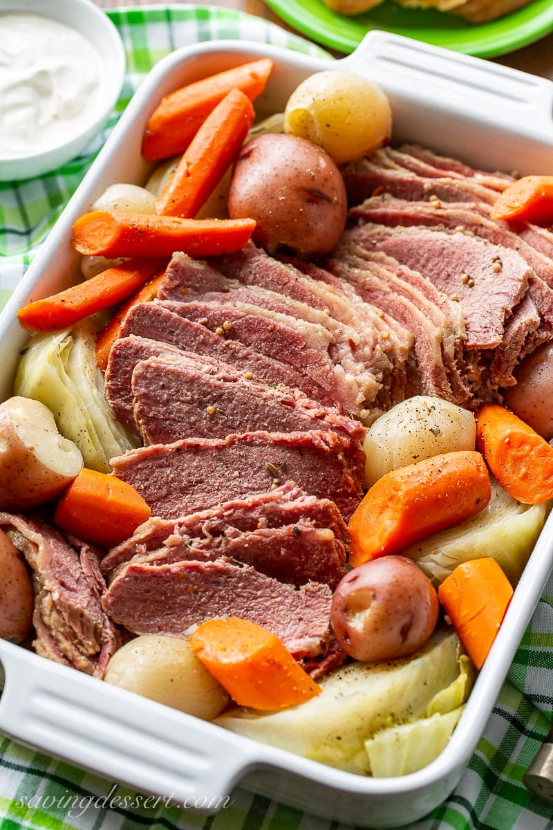 A casserole dish filled with corned beef, cabbage, carrots and potatoes