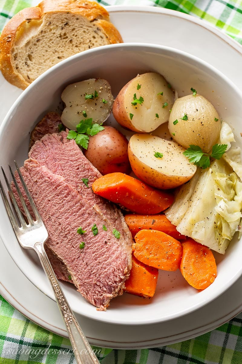 A bowl of corned beef and cabbage served with rye bread
