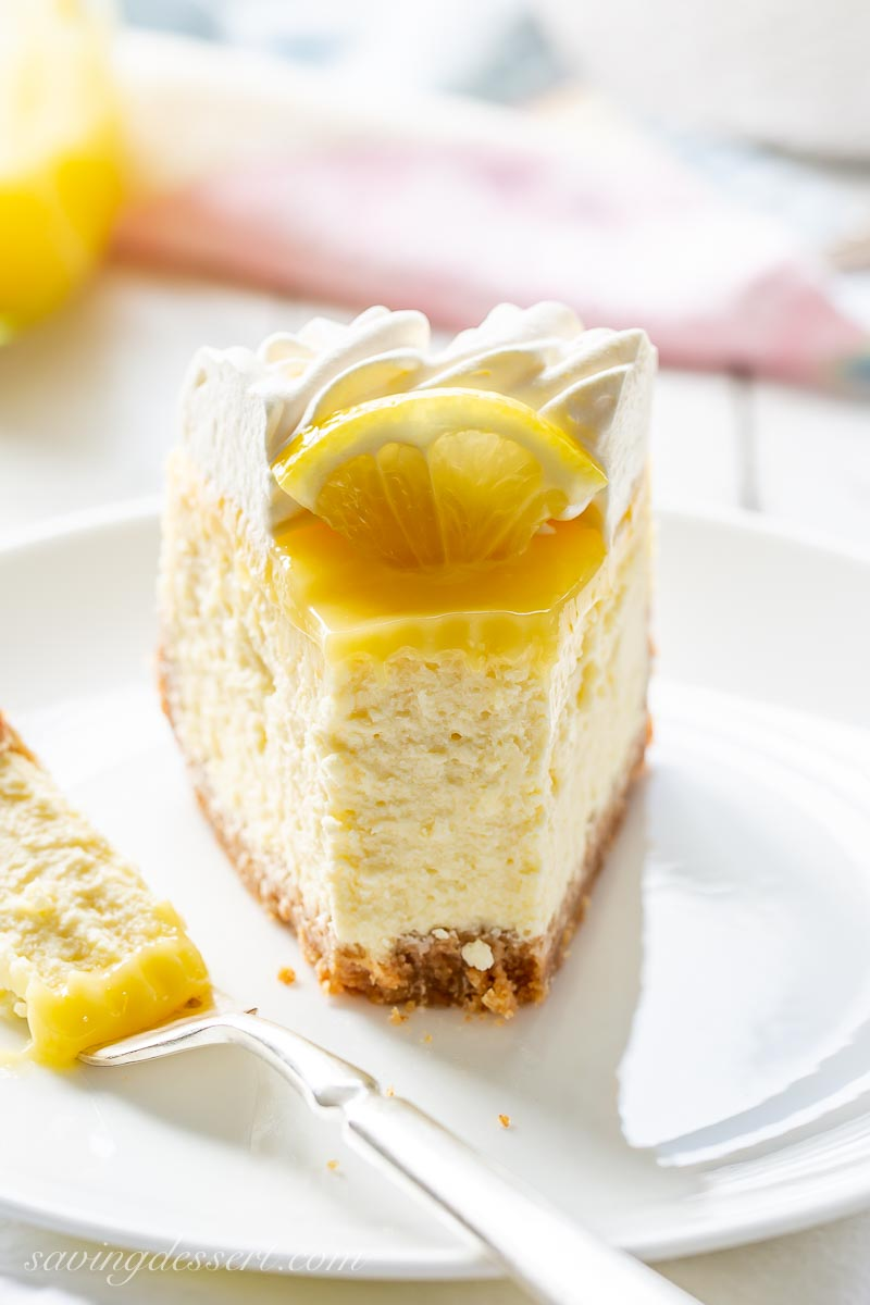 A slice of cheesecake topped with lemon curd and a sliced lemon with whipped cream